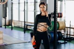 Menina de cabelo escuro magro vestida em suportes pretos do sportswear com água em sua mão perto do equipamento de esporte no gym fotografia de stock royalty free