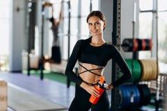 Menina de cabelo escuro magro vestida em suportes pretos do sportswear com água em sua mão perto do equipamento de esporte no gym foto de stock royalty free