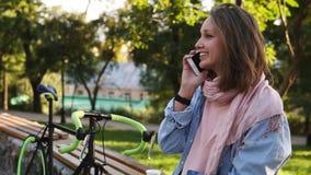 Menina de cabelo justa bonita que senta-se no banco no parque da cidade com sua bicicleta trekking ao lado dela Fala por ela video estoque