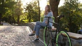 Menina de cabelo justa que senta-se no banco ou no parapeito no parque da cidade com pavimentado sua bicicleta trekking ao lado d filme