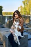 Menina de cabelo marrom bonita que guarda um cachorrinho ronco em seus braços imagens de stock