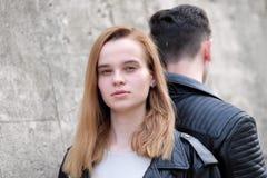 A menina de cabelo vermelha bonita e o indivíduo giraram longe dela imagem de stock