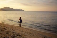 Menina de cabelo vermelha na borda do oceano com braços para fora imagem de stock