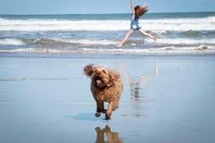 Menina de cabelo vermelha que faz um suporte ou um cartwheel da mão em uma praia da ressaca de Nova Zelândia foto de stock royalty free