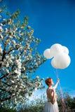 Menina de cabelo vermelha que guarda balões maciços do hélio imagem de stock