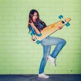 Menina de cabelos compridos bonita com um longboard de madeira perto de um verde Imagens de Stock Royalty Free