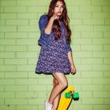 Menina de cabelos compridos bonita com um skate amarelo da moeda de um centavo perto da Fotografia de Stock
