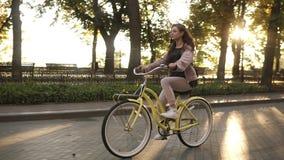 Menina de cabelos compridos bonita da vista lateral que monta uma bicicleta na rua ou no bulevar no parque da cidade do verão Cor filme