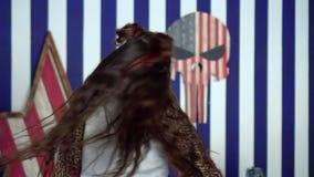A menina de cabelos compridos bonita mostra movimentos da dança A menina bonita dança na frente da câmera nas calças de brim video estoque