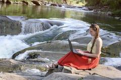 Menina de cabelos compridos bonita na saia vermelha com o portátil que senta-se em uma rocha em um fundo da cascata do rio da mon fotografia de stock
