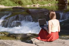 Menina de cabelos compridos bonita na saia vermelha com o portátil que senta-se em uma rocha em um fundo da cascata do rio da mon fotos de stock