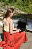 Menina de cabelos compridos bonita na saia vermelha com o portátil que senta-se em uma rocha em um fundo da cascata do rio da mon imagens de stock royalty free