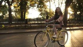 Menina de cabelos compridos bonita que monta uma bicicleta na rua ou no bulevar no parque da cidade do verão Rosa vestindo colori video estoque