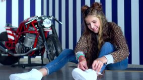 A menina de cabelos compridos bonita senta-se em um assoalho no estúdio e ata-se acima as sapatilhas do branco da soja A menina b vídeos de arquivo