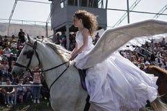 A menina de cabelos compridos com as asas grandes atrás dela para trás está montando em um cavalo branco Imagens de Stock Royalty Free