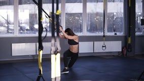 Menina de cabelos compridos da aptidão no sportswear preto que faz exercícios de pés ao guardar correias do peso Squatting, p?s d filme