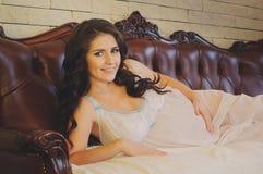 Menina de cabelos compridos da gravidez na camisa de noite que encontra-se na cama em casa Imagens de Stock Royalty Free