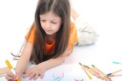 A menina de cabelos compridos desenha uma casa. Fotos de Stock