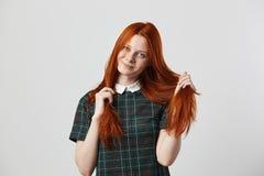 A menina de cabelos compridos do ruivo bonito em um vestido quadriculado verde guarda sua mão em seus cabelos no fundo branco no imagens de stock
