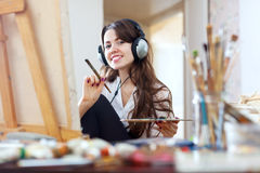 Menina de cabelos compridos em pinturas dos fones de ouvido na lona imagem de stock royalty free