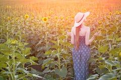 Menina de cabelos compridos em suportes de um chapéu e do vestido com o seu para trás na perspectiva do campo de florescência ens fotografia de stock royalty free