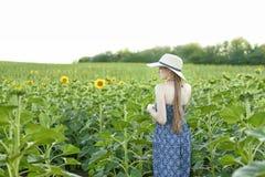 Menina de cabelos compridos em suportes de um chapéu e do vestido com o seu para trás na perspectiva de um campo de florescência  imagem de stock royalty free