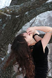 A menina de cabelos compridos está perto de uma árvore, levantando sua cabeça acima Imagens de Stock