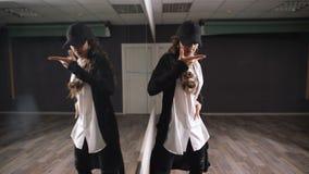 Menina de cabelos compridos na camisa branca, na calças preta e no tampão preto mostrando a dança moderna do jazz-funk na sala de filme
