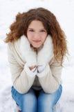 A menina de cabelos compridos nas calças de brim e em um revestimento de pele de carneiro olha no Imagens de Stock Royalty Free