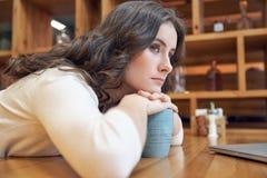A menina de cabelos compridos nova atrativa com uma cara furada dobrada à tabela no café e olha pensativamente na distância fotos de stock