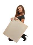 A menina de cabelos compridos prende um poster vazio Fotos de Stock