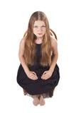 A menina de cabelos compridos que senta-se na cadeira Fotos de Stock Royalty Free