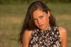A menina de cabelos compridos senta-se na grama Fotos de Stock Royalty Free