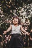 A menina de cabelos curtos bonito pequena joga as folhas imagem de stock