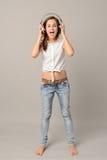 A menina de canto com fones de ouvido escuta música Imagens de Stock Royalty Free
