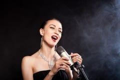 Menina de canto com um microfone fotos de stock royalty free