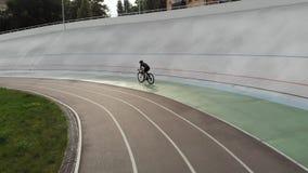 A menina de ciclagem desportivo magro na bicicleta da trilha está treinando no velodrome Mulher atrativa na equitação da biciclet video estoque