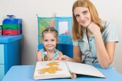 Menina de cinco anos e mãe que olham o herbário das folhas no álbum e olhadas no quadro Fotografia de Stock Royalty Free