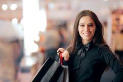 Menina de compra com os sacos dentro da loja na estação da venda foto de stock