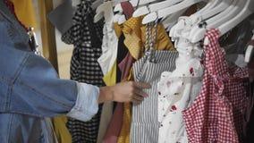 Menina de compra Retrato de uma mulher bonita na loja da roupa Menina loura nova com bordos vermelhos em uma loja de roupa vídeos de arquivo