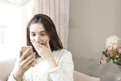 Menina de Confuset que lê uma mensagem em um telefone esperto que senta-se em um sofá em casa fotos de stock