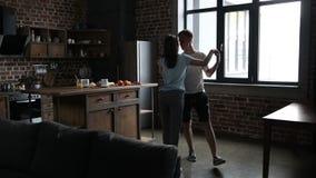 Menina de convite do homem considerável a dançar na cozinha vídeos de arquivo