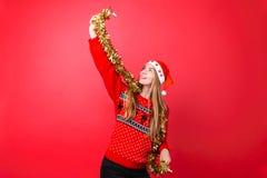 A menina de dança na camiseta vermelha, e o chapéu de Santa, têm o divertimento com ouropel no pescoço, comemorando o ano novo no foto de stock royalty free