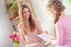 Menina de dia das mulheres da mãe e da filha junto em casa que dá presentes a sua mamã imagens de stock
