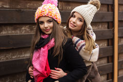 A menina de dois amigos está vestindo a roupa morna do inverno Fotografia de Stock Royalty Free