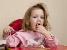 A menina de dois anos come com uma forquilha na tabela na cozinha Imagem de Stock Royalty Free