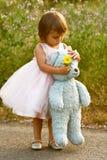 A menina de dois anos elegante na terra arrendada cor-de-rosa do vestido encheu o urso e a flor Fotos de Stock Royalty Free