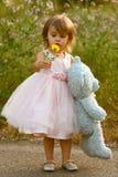 A menina de dois anos elegante na terra arrendada cor-de-rosa do vestido encheu o urso e a flor Fotografia de Stock