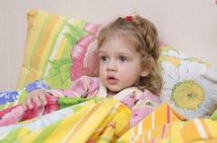 A menina de dois anos está na cama sob a cobertura Fotografia de Stock