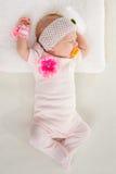 A menina de dois meses dorme na cama nas mãos estendido principais Fotografia de Stock Royalty Free